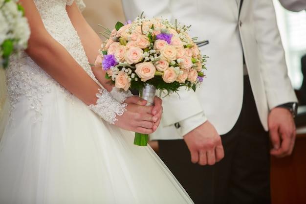Dzień ślubu. nowożeńcy podczas ceremonii ślubnej. panna młoda z pięknym ślubnym bukietem i panem młodym w białym jaket delikatnie trzymając się za ręce. romantyczny moment ślubu. szczęśliwa nowożeńcy z bliska