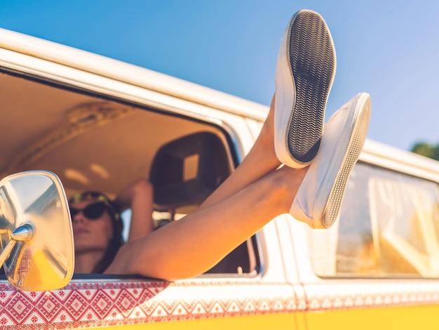 Dzień śni w samochodzie. zbliżenie młodej kobiety trzymającej nogi przez okno, siedzącej wewnątrz minivana