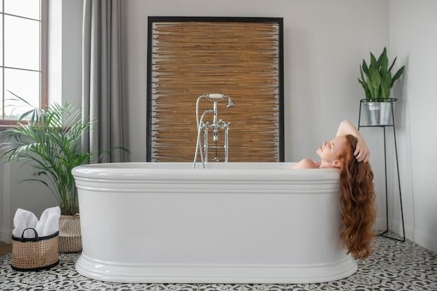Dzień spa. piękna ruda kobieta leży w wannie i wygląda na zadowoloną