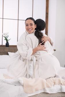 Dzień spa. wesoła przyjaciółka przytulanie się podczas wizyty w salonie spa