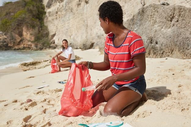 Dzień sprzątania. odkryty poziome strzał z mieszanej rasy młodych kobiet sprzątających plażę z odpadów