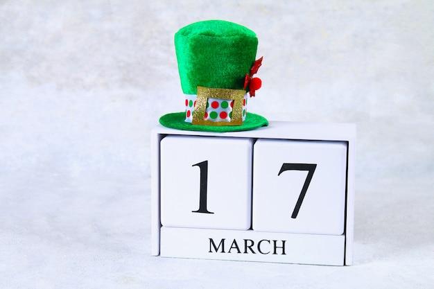 Dzień świętego patryka. drewniany kalendarz z 17 marca. zielony kapelusz i kokardka.