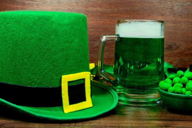 Dzień świętego patryka. kufel piwa z zielonego szkła, zielone słodycze z ciasteczkami i zielony kapelusz krasnal na drewnianym stole