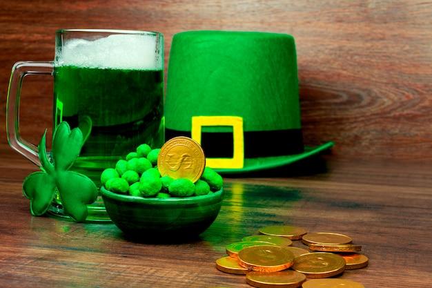Dzień świętego patryka. kufel piwa z zielonego szkła, zielone słodycze z ciasteczkami, zielony kapelusz krasnoludka, zielona koniczyna trzy płatkowa i złote monety na drewnianym stole