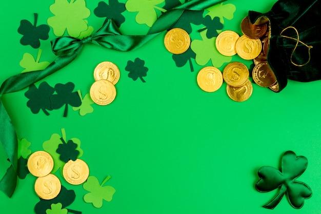 Dzień świętego patryka. zielona zakrzywiona taśma, zielone trzy koniczyny płatkowe i mała torebka ze złotymi monetami krasnoludków na zielonym tle