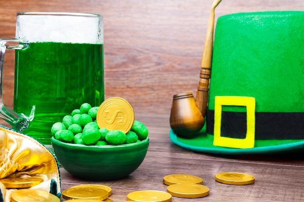 Dzień świętego patryka. zielony kapelusz krasnoludka z zielonym kuflem piwa, złotymi monetami, fajką i zielonymi cukierkami na drewnianym stole