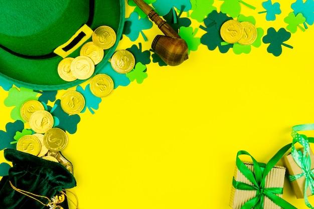 Dzień świętego patryka. złote monety, zielona koniczyna trzy płatek, zielony kapelusz krasnoludek i fajka na żółtym tle