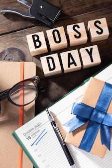 Dzień szefa z widokiem z góry na prezent i notebook