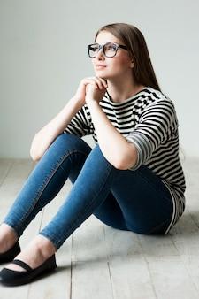 Dzień urody marzy. piękna młoda kobieta w pasiastym ubraniu siedzi na podłodze i odwraca wzrok