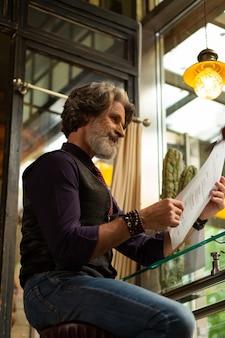 Dzień w kawiarni. uśmiechnięty brodaty mężczyzna siedzący przy stoliku kawiarnianym z menu w dłoniach myślący o wyborze kolejnej filiżanki kawy.