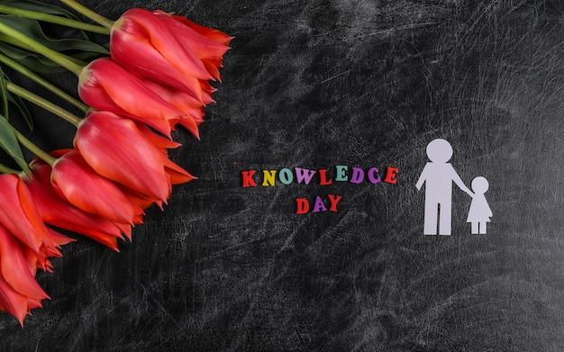 Dzień wiedzy. czerwone tulipany z papierowymi figurami ojciec i córka na tablicy kredowej. widok z góry. powrót do szkoły