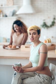 Dzień wolny, kawa. młoda uśmiechnięta kobieta z krótkimi włosami farbowanymi z tatuażem z kawą i czarną dziewczyną z tyłu w kuchni
