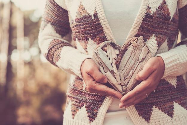 Dzień ziemi z bliska wiadomość z ludzkimi rękami biorącymi drewniane palenisko i zielone piękne nieostre drewniane sosny