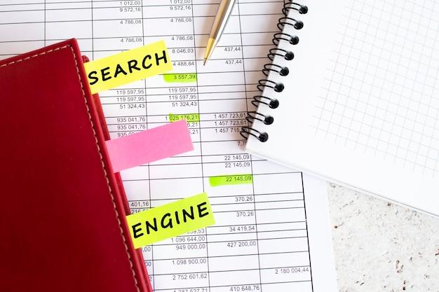 Dziennik biznesowy z kolorowymi zakładkami z napisami leży na wykresach finansowych na biurku