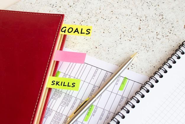 Dziennik biznesowy z kolorowymi zakładkami z napisami leży na wykresach finansowych na biurku.