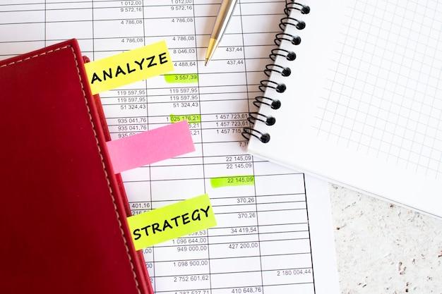 Dziennik biznesowy z kolorowymi zakładkami z napisami leży na wykresach finansowych.