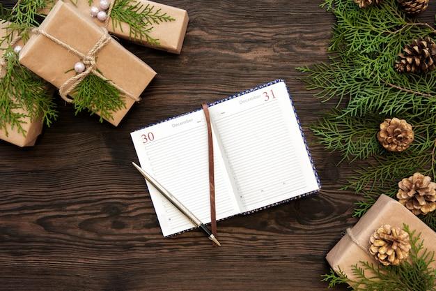 Dziennik jest otwarty na stronie 31 grudnia. notatnik, prezenty, szyszki jodły na drewnianym.