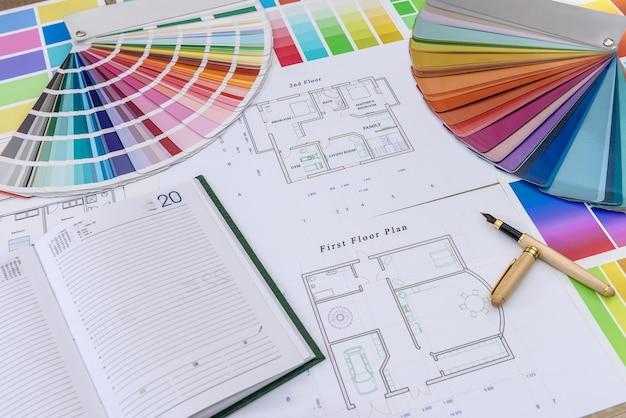 Dziennik z długopisem i próbką koloru na planie domu w biurze