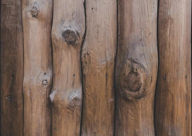Dzienniki są ułożone pionowo. drewniana palisada. drewniana ściana z bali sosnowych jako tekstura tła