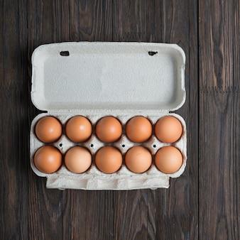 Dziesięć brązowych jaj w papierowym pudełku
