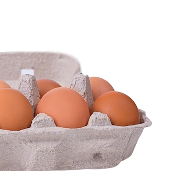 Dziesięć brązowych jajek w tekturowym pudełku.