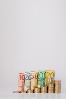 Dziesięć, dwadzieścia, pięćdziesiąt, sto, dwieście i monety euro walcowane rachunki banknoty na białym tle. histogram z euro. pojęcie wzrostu waluty, oszczędności.
