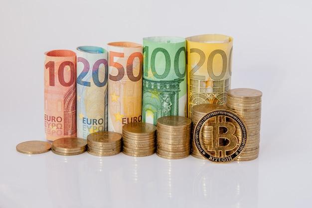 Dziesięć, dwadzieścia, pięćdziesiąt, sto, dwieście i monety euro walcowane rachunki banknoty na białym tle