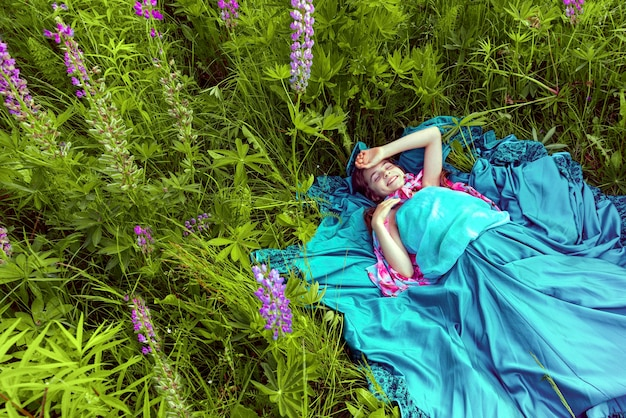 Dziesięcioletnia dziewczynka z długimi włosami i długą niebieską sukienką leży na trawie wśród kwiatów łubinu i uśmiecha się