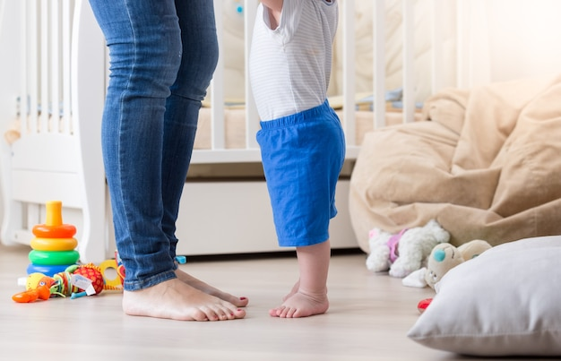 Dziesięciomiesięczne dziecko uczy się chodzić z mamą w salonie