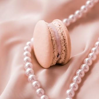 Dziewczęca koncepcja piekarni i brandingu słodkie makaroniki i perły biżuteria na jedwabnym tle paryska szykowna biżuteria francuski deser makaronik do jedzenia i ciasta dla luksusowych wyrobów cukierniczych prezent świąteczny