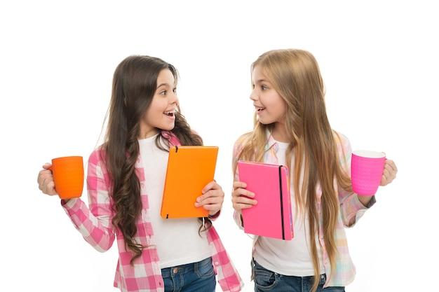 Dziewczęca książka bestsellerów. jaka jest twoja ulubiona historia. nie ma przyjaciela tak lojalnego jak książka. dziewczyna trzymać filiżankę herbaty i książki. literatura dla dzieci. czytanie listy wiader. spędź miło czas z ulubioną książką.