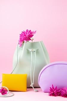 Dziewczęce akcesoria skórzane w jasnych pastelowych kolorach: zła ręka, torebka, torebka do makijażu i kwiaty na różowym tle