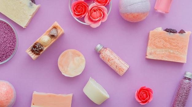 Dziewczęce kosmetyki, produkty do higieny kąpieli spa. różowe kosmetyki kule do kąpieli, koraliki do kąpieli, olejki aromatyczne i mydło z kwiatów róży. mieszkanie leżało na fioletowym tle. kosmetyki higieniczne