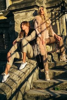 Dziewczęce modelki noszą futrzane ubrania. luksusowy styl życia. ciepłe ubrania. modny strój. modne damskie futra. zmysłowe dziewczyny futro ubrania relaksujący architektura tło. ciesz się luksusem.