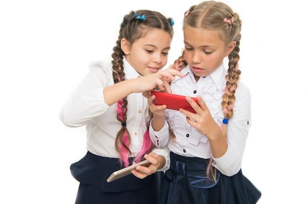 Dziewczęcy mundurek szkolny surfowania po internecie. nowoczesne życie. uczennice korzystają z mobilnego smartfona internetowego. szkolny smartfon aplikacji. uzależnienie od telefonów komórkowych. sieć na całym świecie. zasoby internetowe niosą ze sobą zagrożenia dla dzieci.