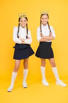 Dziewczęta dzieci obrazujące luksusowy styl życia. koronacja nagrody. świetni uczniowie. uczennice noszą złote korony jako symbol szacunku. nagroda i szacunek. urocza księżniczka. nagroda motywacyjna dla dzieci w wieku szkolnym.