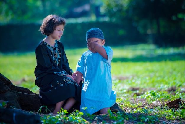 Dziewczęta i chłopcy azjatyccy muzułmanie siedzą i odpoczywają pod drzewem na wakacjach. w ich domu o poranku pięknie świeci słońce.
