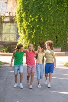 Dziewczęta i chłopcy spacerujący po parku
