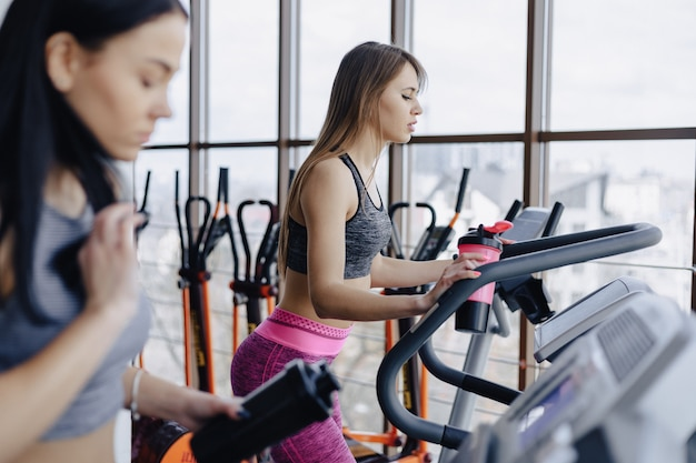Dziewczęta na siłowni są trenowane na bieżniach i piją wodę