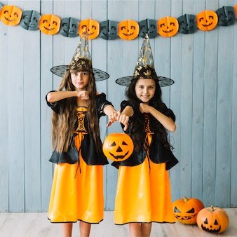 Dziewczęta w szatach czarownic udających trzymające noże za szyje