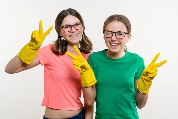 Dziewczęta w żółtych rękawiczkach ochronnych pokazują zwycięstwo.