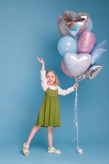 Dziewczyna 5 lat w zielonej sukience z balonami na niebieskiej powierzchni