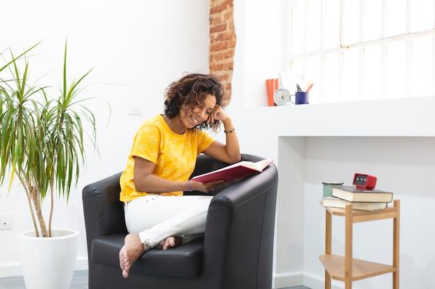 Dziewczyna ameryki łacińskiej, ciesząc się, czytając książkę w domu. miejsce na tekst.