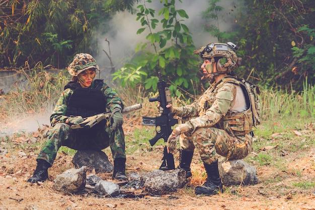 Dziewczyna armii z karabinem siedzi w lesie na polu bitwy.