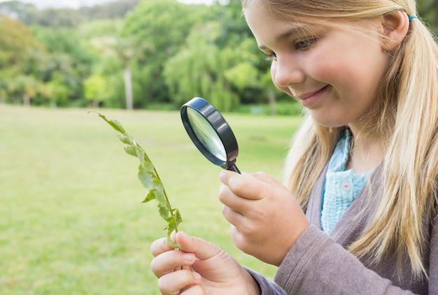 Dziewczyna bada liście z powiększać - szkło przy parkiem
