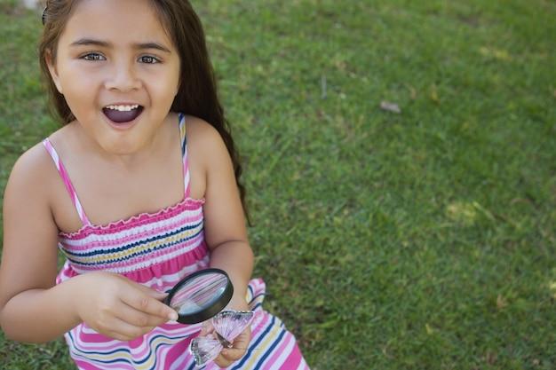 Dziewczyna bada motyla z powiększać - szkło przy parkiem