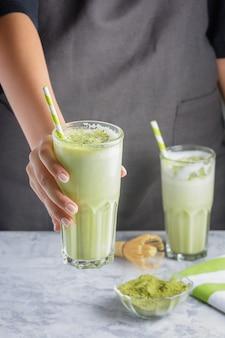Dziewczyna barista podaje szklankę zielonej herbaty matcha.