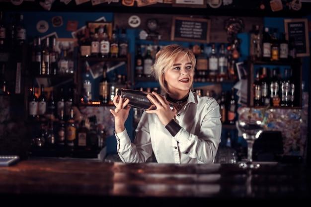 Dziewczyna barman robi koktajl w publicznym domu