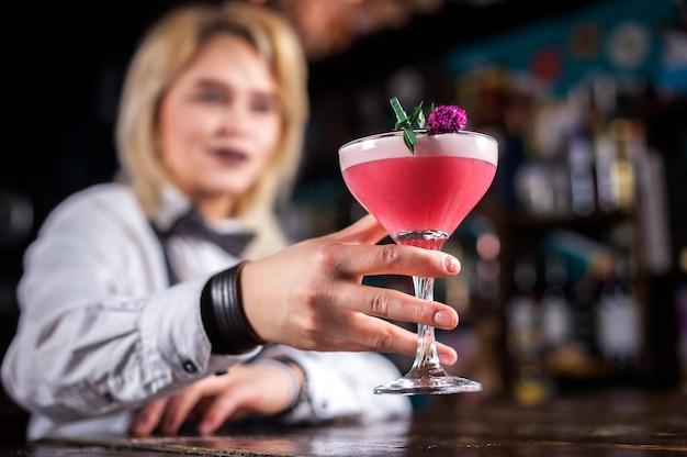 Dziewczyna barmana przyrządza koktajl w brasserie
