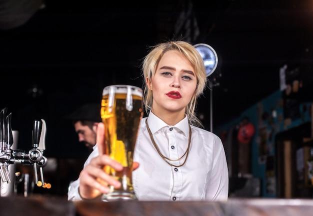 Dziewczyna barmanka przygotowuje koktajl w piwiarni
